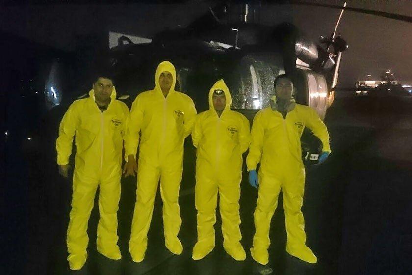 Tripulación de la FAC empleando trajes contra riesgo biológico